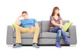 Sad heterosexual couple sitting on a sofa after an argument isolated white background Stock Photo
