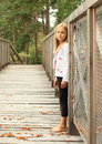Sad little girl on bridge barefoot standing wooden in forest Stock Photography
