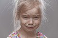 Sad little girl crying beautiful on gray background Stock Photography