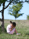 Sad little girl crying in nature child with hands on her face near a small tree Royalty Free Stock Photos
