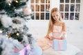 Sad little girl in an elegant pink dress holding gift box near Christmas tree Royalty Free Stock Photo