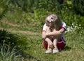 Sad little girl in garden Royalty Free Stock Photos