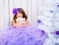 Sad little girl with a gift in hands near white christmas tree Stock Photo