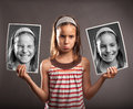 Sad little girl holding two photos of herself portrait with happy expression Stock Photos