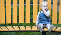 Sad Little Girl sitting alone on a bench. Royalty Free Stock Photos