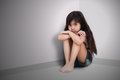 Sad little girl sitting on the floor Stock Photos