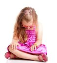 Sad little girl sitting on floor head lowered upset with isolated white Stock Images