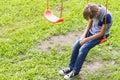 stock image of  Sad lonely boy sitting on swings.