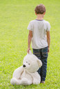 Sad lonely boy with teddy bear standing in the meadow. Child looking down. Back view. Sadness, fear, loneliness concept Royalty Free Stock Photo