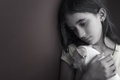 Sad and lonely girl and her small dog leaning against a wall Royalty Free Stock Photography