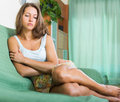 Sad and lonely woman sitting on couch Stock Images