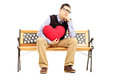 Sad male sitting on a bench and holding a red heart wooden isolated white background Royalty Free Stock Images