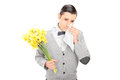 Sad man holding bunch of flowers and crying isolated on white background Royalty Free Stock Photos