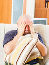Sad man at home sitting on couch hugging pillow Royalty Free Stock Images