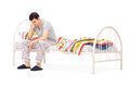 Sad man sitting on a bed and contemplating isolated white background Royalty Free Stock Image
