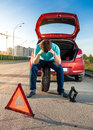 Sad man sitting on spare wheel near broken car portrait of Stock Images