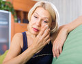 Sad  mature woman sitting on couch Royalty Free Stock Photo