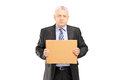 Sad middle aged businessman holding a piece of cardboard and loo looking at camera isolated on white background Royalty Free Stock Photo