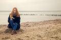 Sad pensive woman on autumn sea beach sitting Royalty Free Stock Images