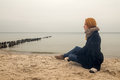 Sad pensive woman on autumn sea beach sitting toned image Royalty Free Stock Photos