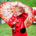 Sad pretty little girl in red raincoat with umbrella walking in park summer Royalty Free Stock Photo