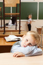 Sad schoolboy in classroom is sitting the half empty after classes he is bored Stock Images