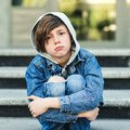 Sad schoolboy sitting alone at stairs outside. Bullying, discrimination and depression concept. Boy in stress. Back to school Royalty Free Stock Photo