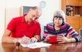 Sad senior couple calculating budget family at home interior Stock Photography