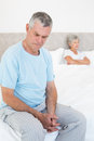 Sad senior man on bed with wife in background men sitting at home Royalty Free Stock Photo