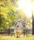 Sad senior man with cane sitting on bench in a park wooden sunny day shot tilt and shift lens Royalty Free Stock Image