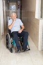 Sad senior man sitting in a wheelchair full length of depressed at hospital corridor Royalty Free Stock Images