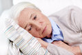 Sad senior woman lying on pillow at home Royalty Free Stock Photo