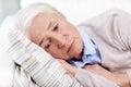 Sad senior woman lying on pillow at home Royalty Free Stock Photo