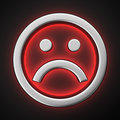 Sad smiley with backlight effect on the black background Stock Photo