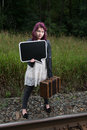 Sad teen girl with black chalk board for your text wait by traintracks Stock Photo