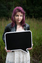Sad teen girl with black chalk board for your text wait by traintracks Stock Photos