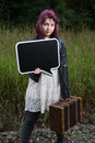 Sad teen girl with black chalk board for your text wait by traintracks Royalty Free Stock Image