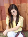Sad teen girl a depressed lonely teenage with long dark hair and yellow blouse against a rustic red background Royalty Free Stock Image