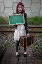 Sad teen girl with green chalk board for your text wait by traintracks Royalty Free Stock Photography