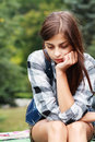 Sad teenage girl outdoor portrait of a looking thoughtful about troubles Stock Photo