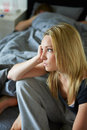 Sad teenage girl sitting in bedroom whilst boyfriend sleeps background bed Royalty Free Stock Photos
