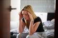 Sad Teenage Girl Sitting In Bedroom Whilst Boyfriend Sleeps Royalty Free Stock Photo