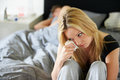 Sad teenage girl sitting in bedroom whilst boyfriend sleeps holding tissue crying Royalty Free Stock Images
