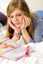 Sad teenage girl because unrequited love lying over her diary Stock Images