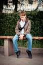 Sad teenager sitting on bench in park teen Stock Photo