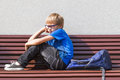 Sad, tired child sitting alone on the bench outdoors. Royalty Free Stock Photo
