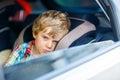 Sad tired kid boy sitting in car during traffic jam Royalty Free Stock Photo