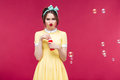 Sad unhappy young woman standing and blowing soap bubbles Royalty Free Stock Photo