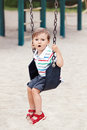 Sad upset worried little small boy toddler in tshirt and jeans shorts on swing on backyard playground Royalty Free Stock Photo