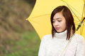 Sad wistful young asian woman walking along outdoors under a yellow umbrella staring disconsolately at the ground Stock Photos